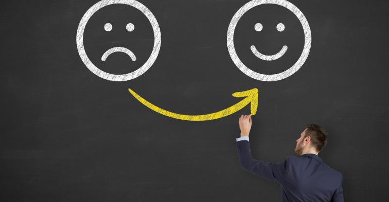 man drawing line from frown face to smiley face