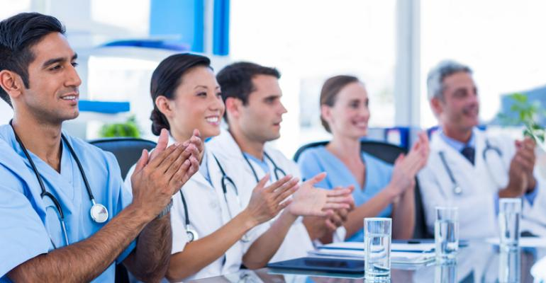 Physicians applauding at a meeting