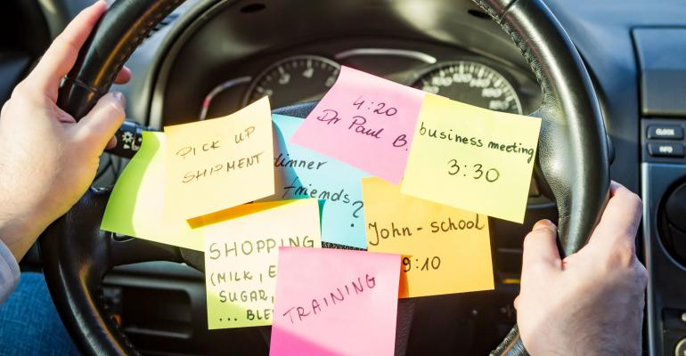 sticky note to-do list on a steering wheel
