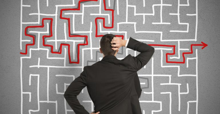Man scratching head in front of maze