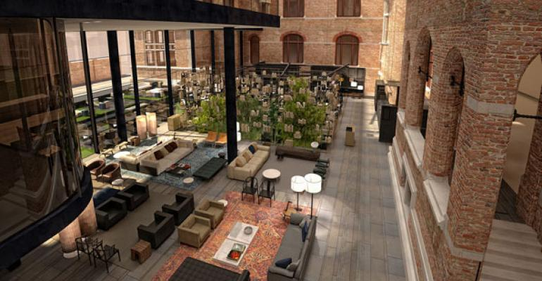 The lobby at Conservatorium Hotel Amsterdam features exposed brick and wood beams of the former music conservatory