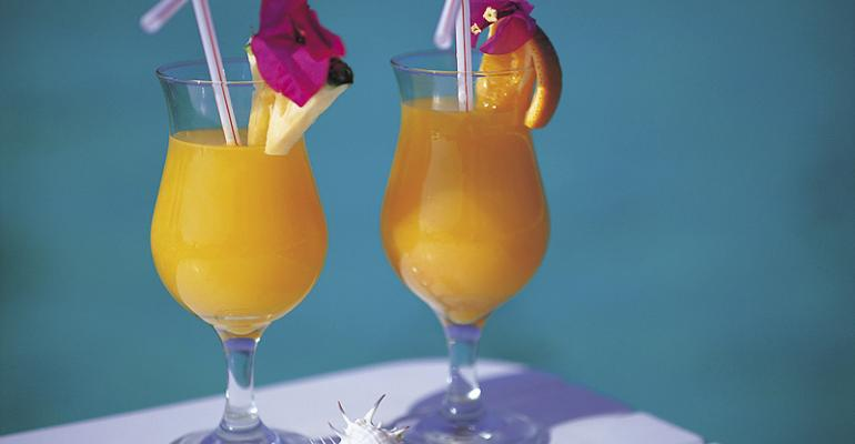 Two glasses of orange juice with pineapple slices and straws