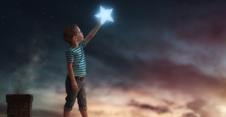 Boy on rooftop touching a star