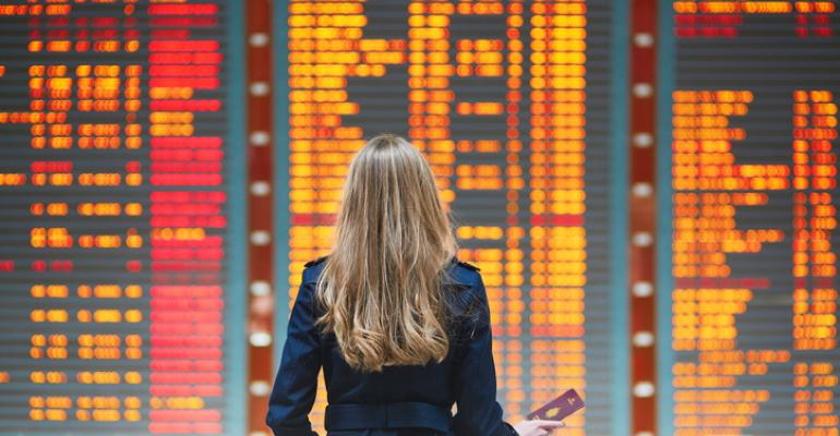 Woman traveler in front of international airport departure board