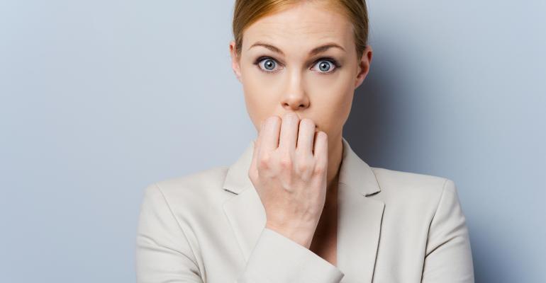 Business woman biting fingernails nervously