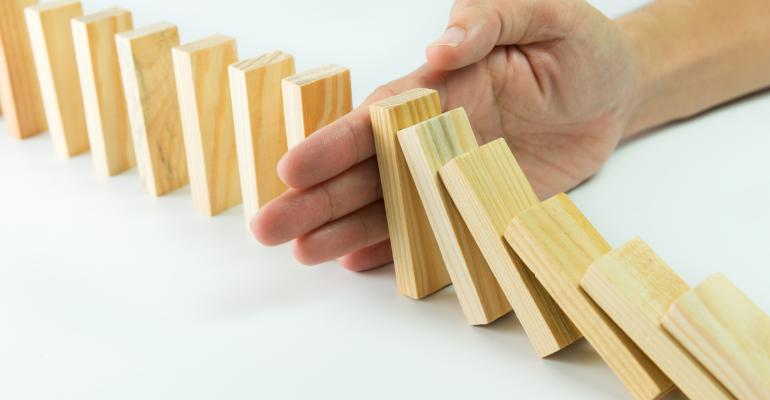 Solution concept with hand stopping wooden blocks from falling in the line of domino