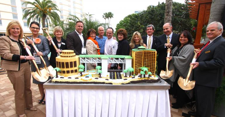 The Gary Sain Memorial Skybridge cake cutting ceremony Pictured left to right Victoria Hall Rosen Plaza Yulita Osuba OCCC Jan Addison OCCC Scott Boyd Orange County Commissioner Teresa Jacobs Orange County Mayor Harris Rosen Rosen Hotels amp Resorts David Ramirez executive pastry chef Rosen Hotels amp Resorts Pamela Sain Maria Triscari International Drive Chamber of Commerce Pete Clarke Orange County Commissioner George Aguel Visit Orlando Leslie Menichini Rosen Hotels amp Resorts Gary Hudson Rosen Plaza