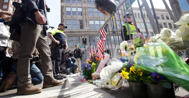 People leave flowers and flags to honor those injured and killed by the Boston Marathon bombing