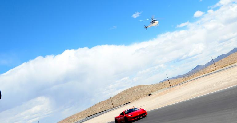 Cars racing on SPEEDVEGAS track with helicopter overhead